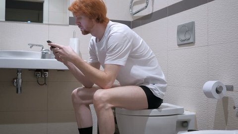 Redhead Man Using Smartphone in Toilet, Commode