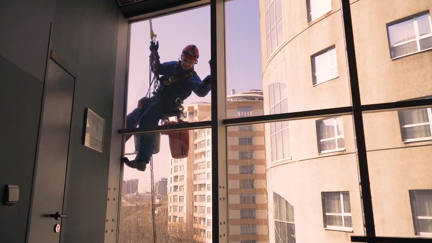 climber washes windows in a skyscraper