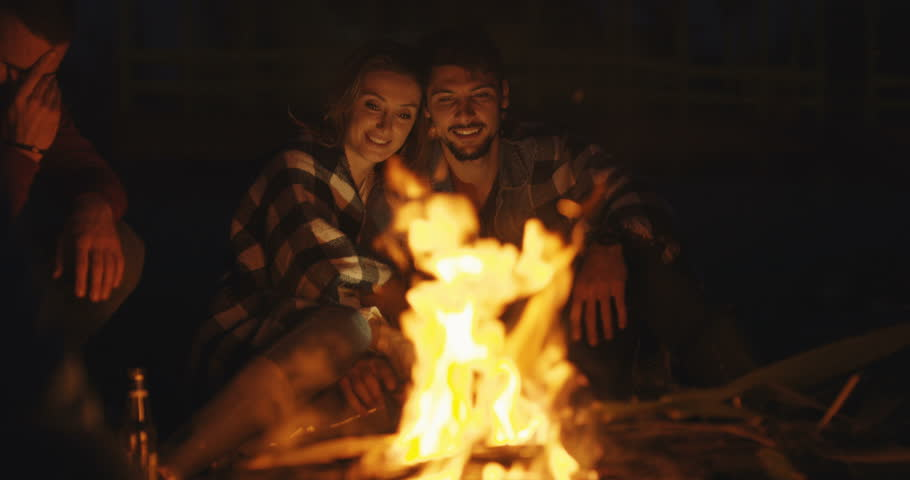 Couple enjoying with friends and drinking beer at night at beach