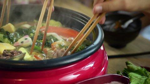 The hand with chopsticks to boil enjoy eating Shabu Shabu and Sukiyaki in hot pot at japanese restaurant.it funny time for eat with friends and family
