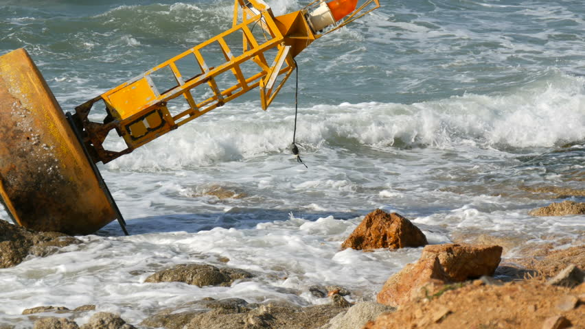 A large yellow buoy on the shores of azure sea. The waves hit the buoy and the big rocks on the shore