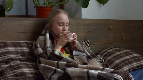 Pretty little sick girl with sore throat wrapped in warm blanket sititng on  the bed and drinking hot tea  adorable sick child with high fever coughing  and taking a medicine in the bed