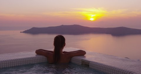 Woman In Swimming Pool Spa Enjoying Sunset On Over Sea Luxury Vacation Travel On Santorini, Greece, Europe. Girl in bikini watching beautiful view of sunset enjoying her holidays at resort hotel.