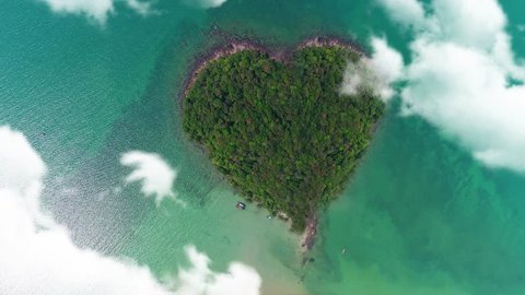 AERIAL. Camera moving trought clouds to heart shape island in Thailand.