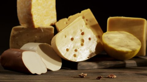 Cheese varieties. Different types of cheeses with milk jug on wooden table. Dolly shot high contrast