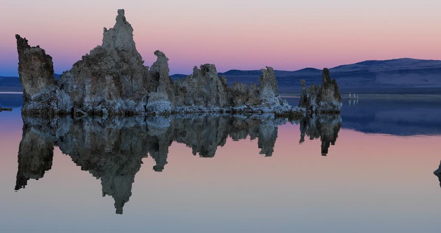 Mono lake tufas with reflection in calm water on sunset with zoom out effect
