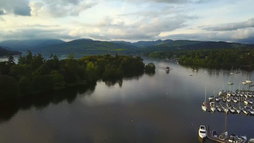 Aerial video of boat cruising along lake Windermere at sunset