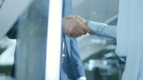 Close-up of the Businesswoman and Businessman Shaking Hands with Emphasis on the Handshake. Shot on RED EPIC-W 8K Helium Cinema Camera.