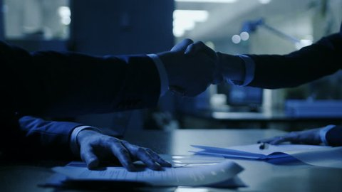 In the Dark Late Night Office Close-up on Hands of Businesswoman and Businessman while Signing Contracts and Shaking Hands. Shady Deal, Inside Trading. 4K UHD
