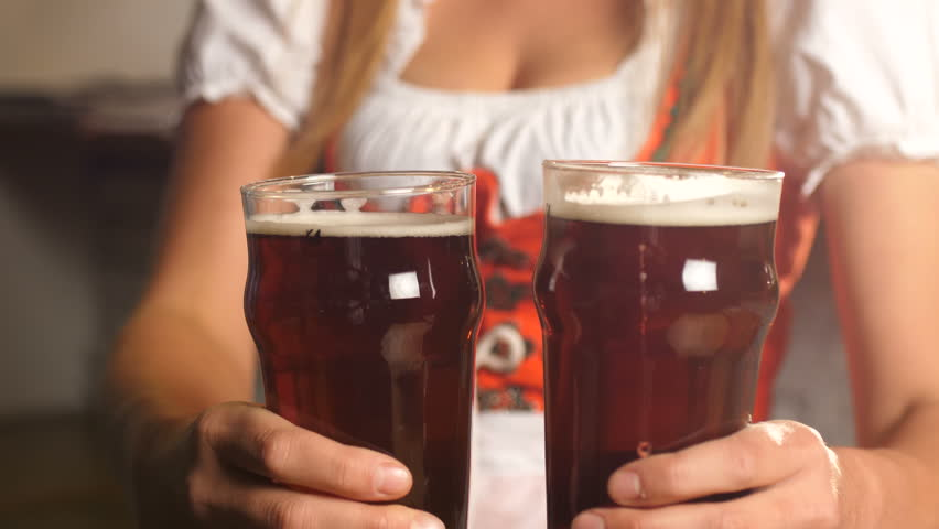 Oktoberfest. Girl puts two glasses of beer on a wooden table.