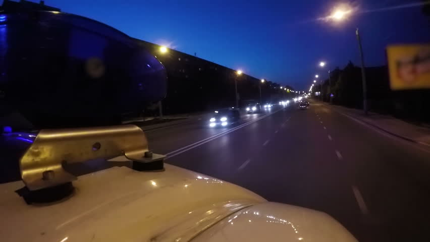 Lights of moving ambulance car flashing in twilight town, high speed necessity