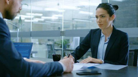 In the Office Businesswoman and Businessman Have Conversation, Negotiating, Draw up a Contract, Sign Documents, Finish Transaction, Shake Hands. Stylish People in Modern Conference Room. 4K UHD.