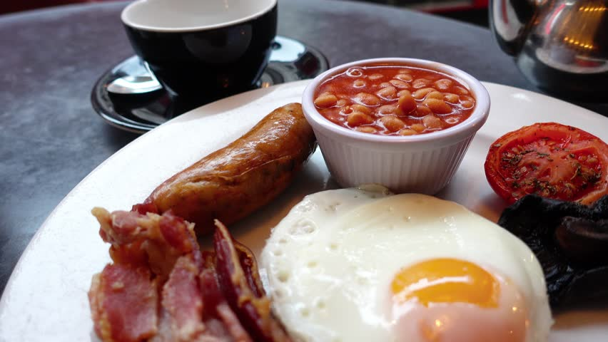 Eating full english breakfast in London, UK. Pouring tea into the cup. Close up, personal perspective, messy eating with baked beans,sausage,eggs and tea.