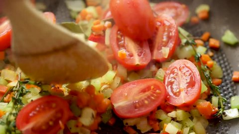 Tomato, capers, onions, carrot, celery cooking on hot pan with white wine