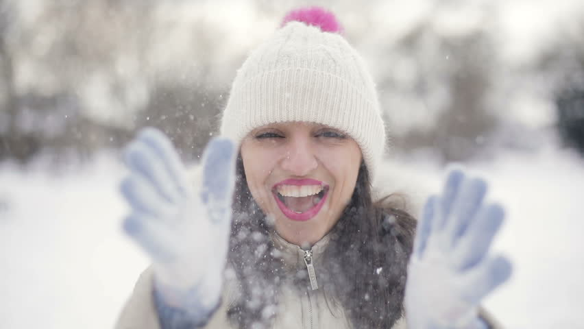 Closeup Brunette hair young women portrait with pink lips in beige down coat and hat throws up snow and smiling  in snowy central park, snowfall. Slow motion.   Shutterstock HD Video #1008002362