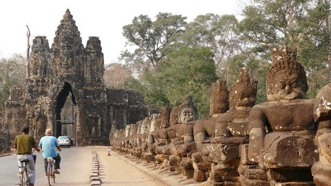 Group of cyclists on the background of the main gate of ancient Angkor Wat temple in Cambodia.