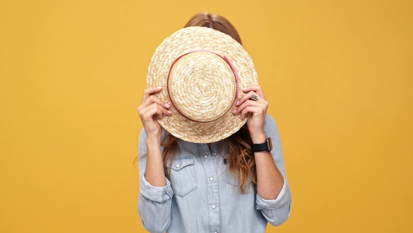 Smiling ginger woman in denim shirt hiding behind a hat and looking at camera over yellow background