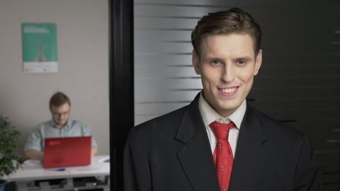 Young successful man in a suit smiles and looks at the camera, portrait. A man works on a computer in the background. 60 fps