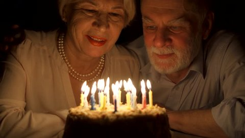 Loving senior couple celebrating anniversary with cake at home in the evening. Happy elderly family hugging, cuddling together, make wishes and blowing out candles.