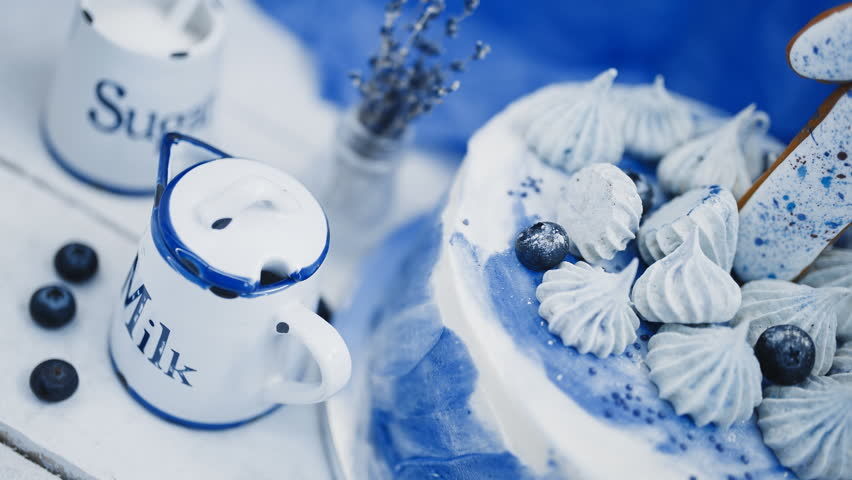 Jug of milk and cake on a blue background next to a vase with branches of lavender.