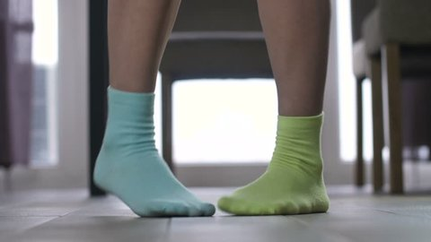Female feet in dancing indoors in socks of different color  woman making  funny funky dance moves with legs and feet in mismatched socks at home