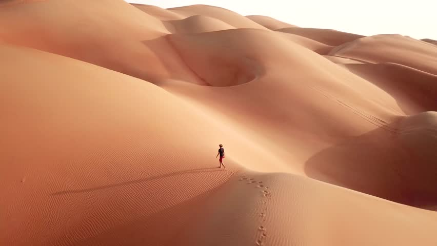 Aerial drone view of a slim man in casual clothes hiking in giant Empty Quarter sand dunes. Abu Dhabi, UAE.