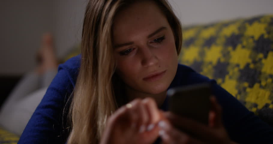 4K Girl checking her smartphone at night, her face illuminated by light from the screen