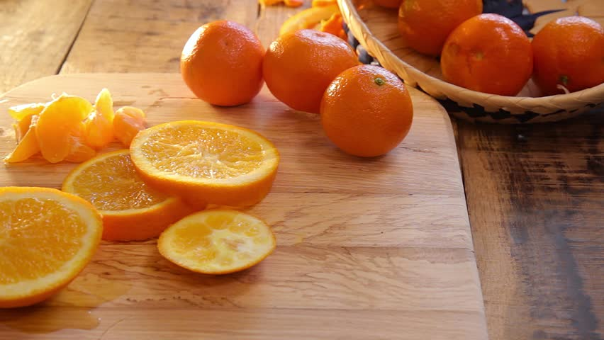 cutted oranges and tangerines on wooden background.