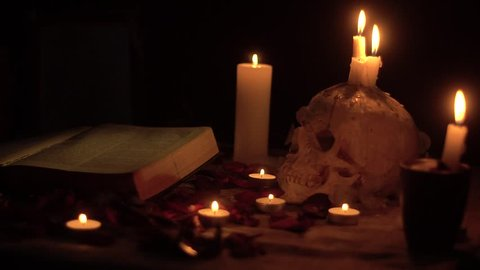 Flashing candle fire on the skull and around the magic book