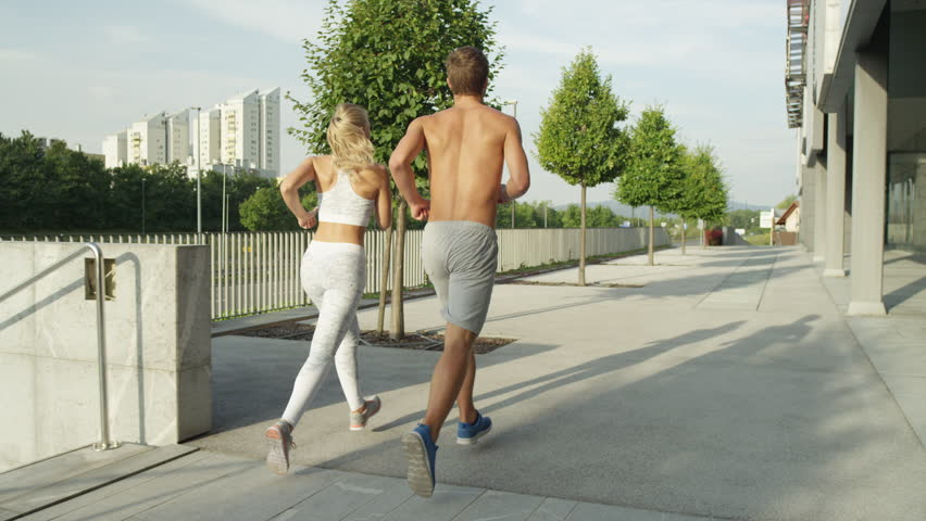 SLOW MOTION CLOSE UP: Unrecognizable athletic couple jogging along city streets on sunny morning. Sporty boy and girl exercising after long day in office. Energetic man and wife working out together | Shutterstock HD Video #1008074842
