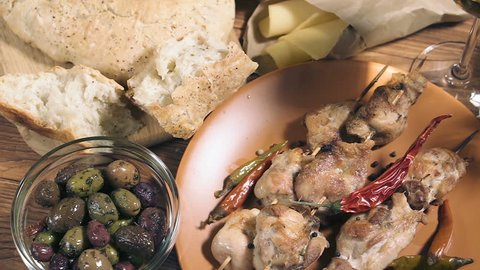 Grilled chicken meat, bowl with different kind of olives, glass of wine, cheese and fresh bread ciabatta on the wooden table, panning shot.