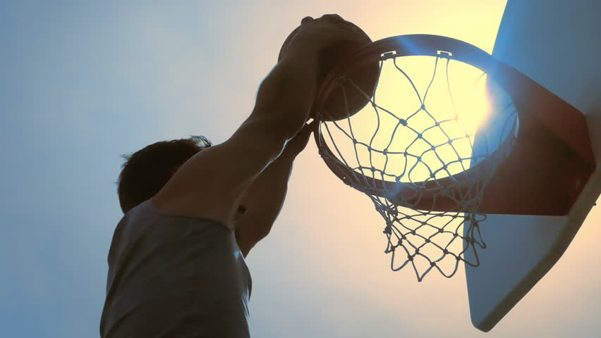 Basketball player scoring slam dunk outdoors in slow motion