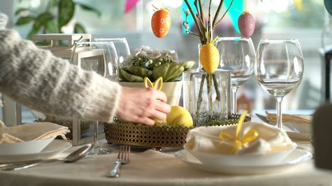 Young woman is setting easter festive table with bunny and eggs decoration