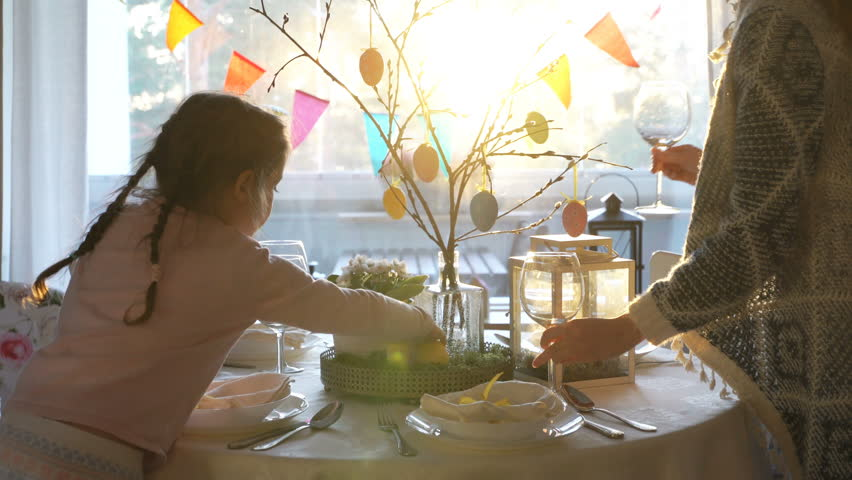 Young woman and her little daughter are setting easter festive table with bunny and eggs decoration