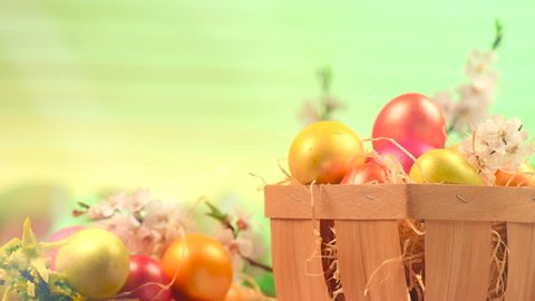 Easter Eggs and spring flowers in a basket on a table over green background. Rotated Beautiful colorful eggs decorated and painted. Spring Holidays border art design 4K UHD video 3840X2160