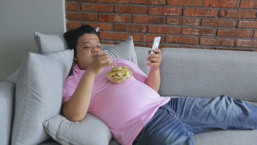 Picture of greedy person feels hungry and eat snack while leaning on the couch using smart phone