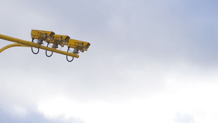 Low angle view of three yellow color average speed cameras against cloudy sky