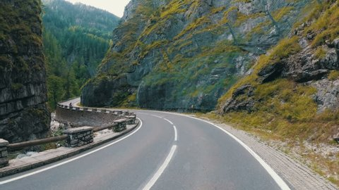 Motorcyclist Rides on a Beautiful Landscape Mountain Road in Austria. First-person view. POV.