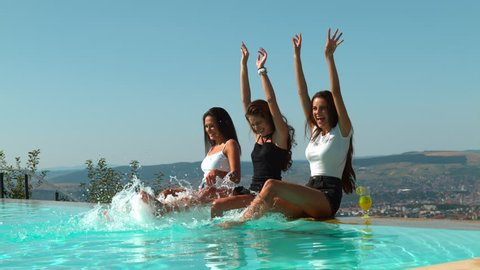 Three young women having fun at a pool party