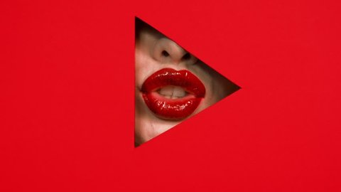 Chubby beautiful girl lips in triangular hole of paper red background. Bright red lipstick on lips of woman. Girl shows her lips in the keyhole. Button play. Concept of advertising cosmetics.