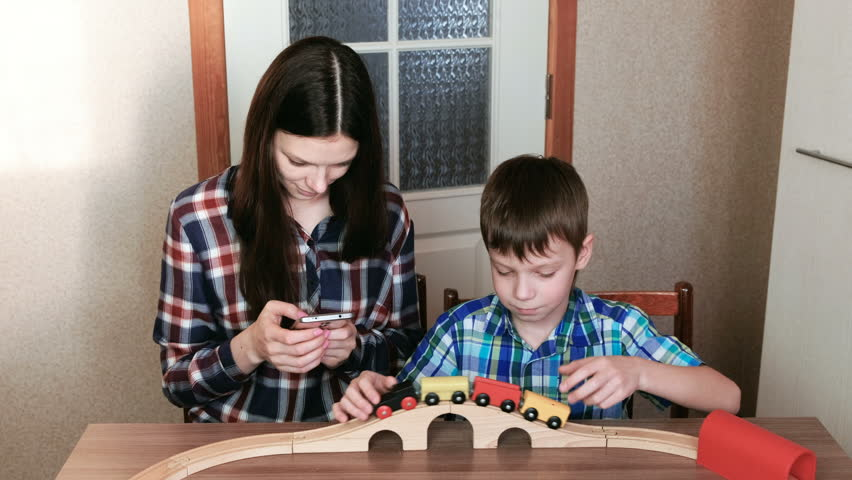 Playing together. Mom looks at phone and son is playing a wooden railway with train, wagons and tunnel sitting at the table.