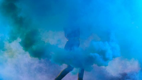 4K Girl is dancing a new style disco contemporary party solo dance with blue color smoke grenade in her hand. Slow motion (150fps) Shooted on Black Background (high quality)