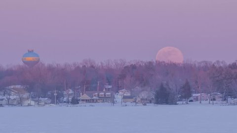 A Telephoto Shot of a Full Moonrise Over a Rural Winter Minnesota Landscape at Dusk