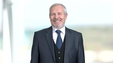 Elderly businessman is laughing, blurred background. Joyful mature businessman is laughing. Funny senior entrepreneur.