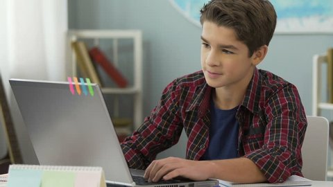 Teenager successfully doing practical work for programming lesson using laptop