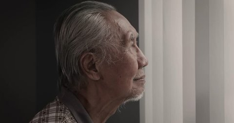Slow motion footage of an elderly man smiling at the camera while standing near the window at home. Shot in 4k resolution