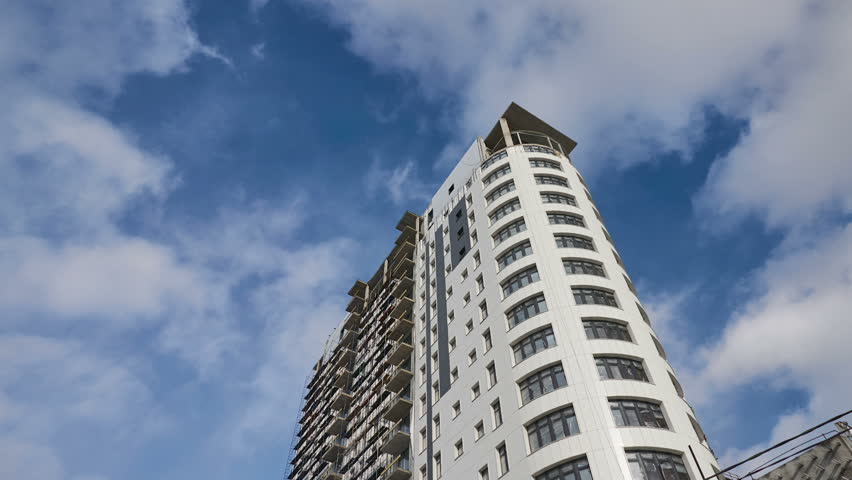 Timelapse finishing of a facade of the building of the high-rise building the bottom view against the background of clouds | Shutterstock HD Video #1008208642