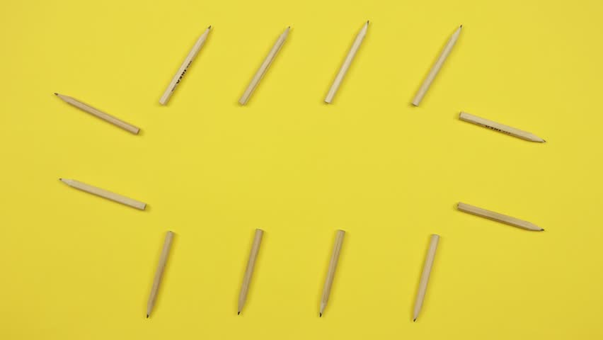 Stop motion animation of appearing color wooden pencils on the table with yellow background.