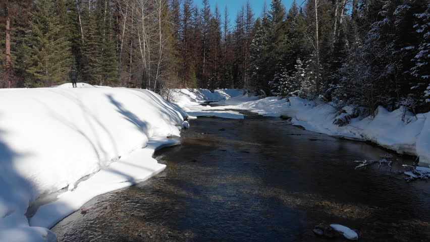 Flyover a snowy winter stream in Montana.