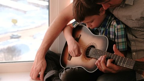 Playing a musical instrument. Dad teaches his son to play the guitar, sitting on the windowsill.